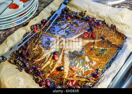 Leere Backblech mit zwei Gabeln Backpapier und Reste nach dem Rösten Hähnchen mit orangen Preiselbeeren und Gewürzen. - Stockfoto