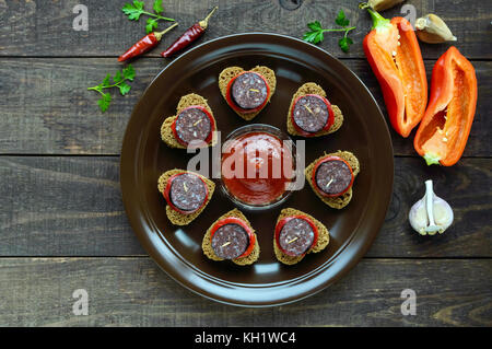 Sandwiches mit schwarzem Roggenbrot in der Form eines Herzens, Blutwurst (morcillo) und Stücke von Paprika auf Spieße - Stockfoto