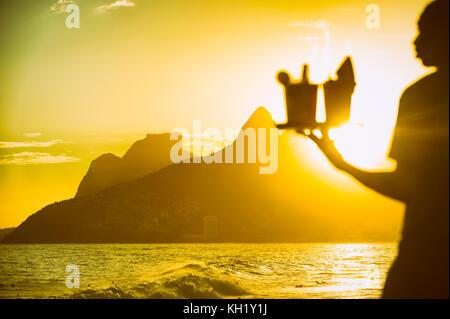 Defokussierten brasilianischen Strand Anbieter Durchführung caipirinha Cocktails in arpoador mit einem Blick auf den Sonnenuntergang von zwei Brüdern Berg in Rio de Janeiro, Brasilien