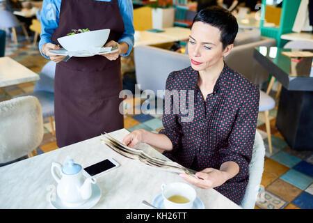 Portrait von eleganten, modernen Frau liest im Cafe Tabelle mit unkenntlich Kellnerin ihre Reihenfolge bringen. - Stockfoto