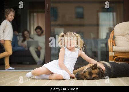 Kleine Mädchen spielen mit Hund draußen, Streicheln deutsche Hirte liegend auf der Veranda, Eltern mit kleinen Jungen - Stockfoto