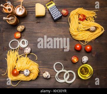 Zutaten zum Kochen Vegetarische Nudeln mit Tomaten, Zwiebeln, Parmesan, eine Vielzahl von Gewürzen auf rustikalen - Stockfoto