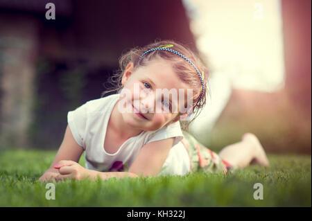 Lächelnde Mädchen in weißem Kleid Festlegung auf frischem Rasen - Stockfoto