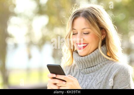Porträt einer Frau tragen Pullover Lesen von Text auf einem Mobiltelefon im Winter - Stockfoto