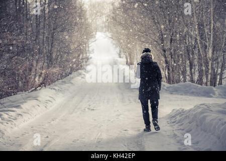 Einsame Frau zu Fuß auf verschneite Straße zwischen Bäumen Gasse mit Licht am Ende des Weges in kalten Wintertag - Stockfoto