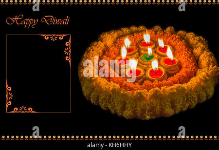 Diwali Ton diya Lampen mit Blumenschmuck in dunklen Hintergrund - Stockfoto