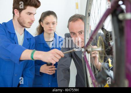 Manager prüfen Fahrrad neben Auszubildenden - Stockfoto