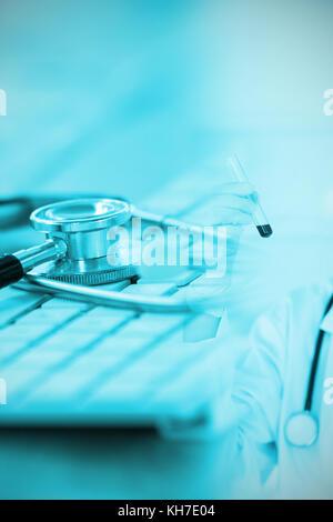 In der Nähe der Tastatur mit Stethoskop gegen blonde Wissenschaftler mit einer Maske in einem Reagenzglas suchen - Stockfoto