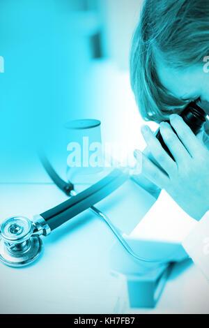 Stethoskop auf dem Schreibtisch gegen konzentrierte Wissenschaftlerin Blick durch ein Mikroskop - Stockfoto