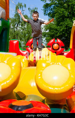 Junge springen auf aufblasbaren Spielplatz - Stockfoto