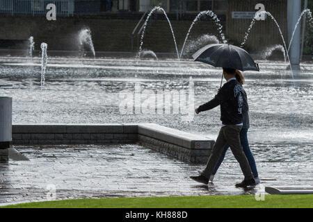 Paar im schweren Regen, schützende unter dem Dach, vorbei an den Spiegel Pool & Brunnen - Bradford City Center Park, - Stockfoto