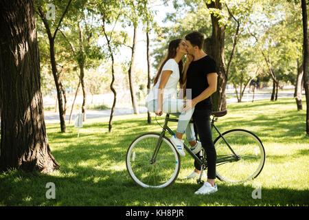 Junge attraktive Paar küssen einander, während ein Mädchen im Sitzen auf einem Fahrrad im Freien - Stockfoto