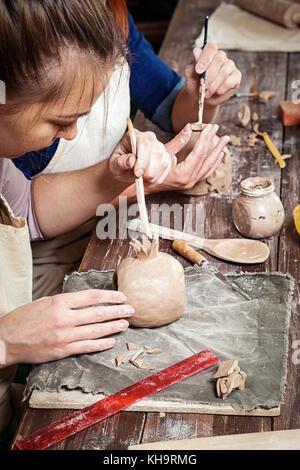 Töpferei Lektion: eine Frau potter malt ein Leuchter aus Ton, und eine andere Frau formt einen Leuchter auf einem Holztisch mit Tools, Bürsten in einem Beau