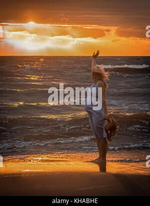 Schwangere Mitte der erwachsenen Frau am Strand bei Sonnenuntergang - Stockfoto