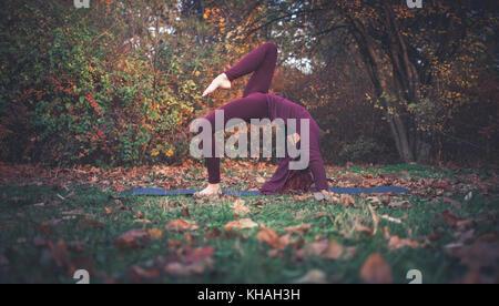 Mädchen auf einen Herbst Tag Üben Yoga im Freien, Variation der Einbeinigen invertiert Personal darstellen (Eka - Stockfoto
