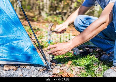 Junger Mann Einrichten camp Zelt für Camping Trip auf Campingplatz durch Hämmern Nagel auf den Boden mit einem Hammer - Stockfoto