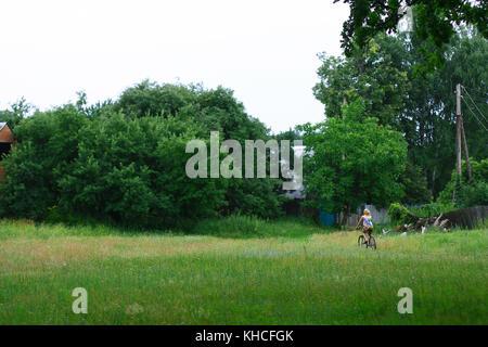 Horizontale Foto der schönen blonden Mädchen reiten ihr Fahrrad in einem Dorf