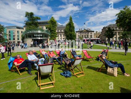 Kunden in Liegestühlen außerhalb der Costa Coffee Shop in St Andrew Square, Edinburgh, Schottland entspannen. - Stockfoto