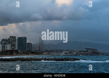 Panorama viiew von Barcelona's Wharf mit Strand und Stadt im Hintergrund in einem trüben stürmischen Nachmittag - Stockfoto