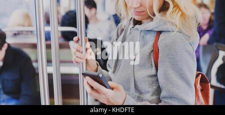 Person auf dem Bildschirm des smart phone in der Nähe der U-Bahn, Frau mit Handy in der U-Bahn - Stockfoto