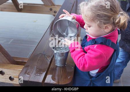 Kleines Mädchen gießt Wasser aus einem Eimer zu einem anderen - Stockfoto