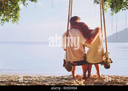 Einen romantischen Urlaub für Zwei, zärtlich Paar zusammen sitzen am Strand auf Swing, Silhouette des Menschen umarmt - Stockfoto