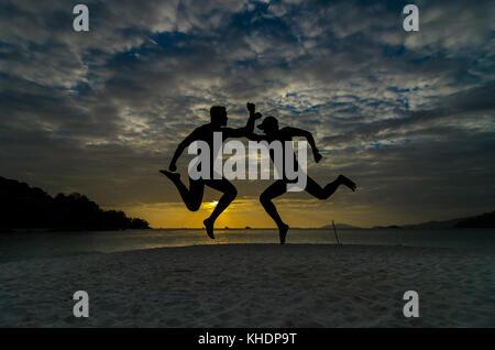 Zwei Freunde über das Meer Strand mit Sonnenuntergang - Stockfoto