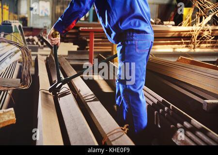 Arbeiter in einer weißen Helm beißt den Stahldraht mit Drahtschneider - Stockfoto