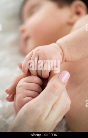 Schlafendes Baby holding Mama's Finger. Mutterschaft und Kindheit Konzept. - Stockfoto