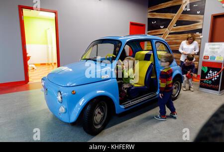 Ein kleines Mädchen vorgibt, ein Fiat 500 im Musee D'Enfance indoor themed Play cenrtre in Laval, Quebec zu fahren - Stockfoto