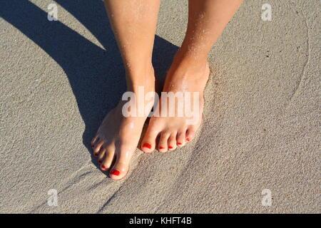 Die Füße und die lackierten Nägel der jungen Frau, in den Sand und Wasser stehen. - Stockfoto