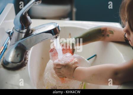 Ein Kleinkind Mädchen waschen Farbe weg die Hände in einem Waschbecken im Bad. - Stockfoto