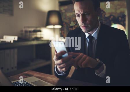 Eine nachdenkliche intelligente Manager im Büro zu sitzen und sein Smartphone surfen. - Stockfoto