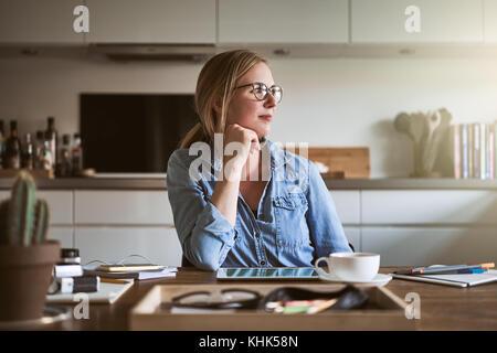 Junge weibliche Unternehmer durch ein Fenster, während an einem Tisch in ihrer Küche zu Hause arbeiten - Stockfoto