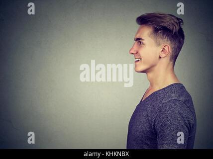 Seite Profil Portrait eines glücklichen Menschen auf grauem Hintergrund lachen - Stockfoto