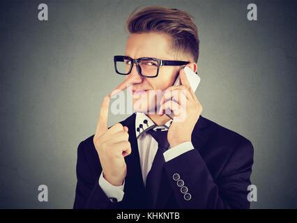 Junge sly Mann mit langen Nase Gespräch am Handy auf grauen Hintergrund isoliert. Lügner Konzept. menschlichen Emotionen - Stockfoto