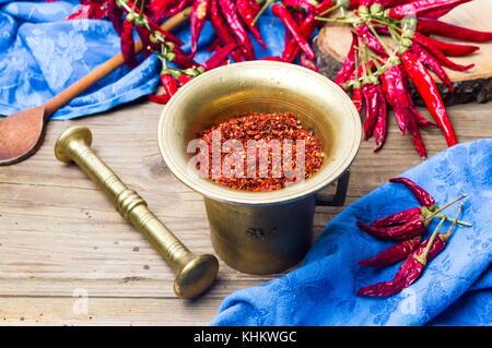 Boden und ganze rote Paprika in einem vintage Mörtel - Stockfoto