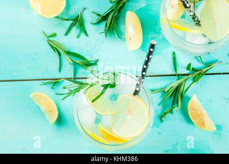 Kalte Limonade oder Alkohol Wodka Cocktail mit Zitrone und Rosmarin, auf hellblau Tabelle, kopieren Raum - Stockfoto