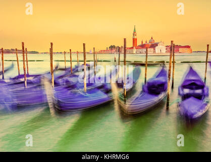 Die Gondeln bewegen entlang der Kurve auf dem Canal Grande in Venedig bei Sonnenuntergang. - Stockfoto