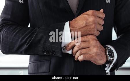 Nahaufnahme der Geschäftsmann in Anzug Korrektur eine Hülse. Männliche Hände zur Festsetzung weisses Shirt Bündchen - Stockfoto