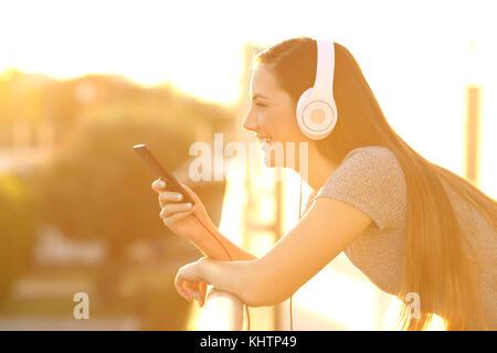 Seitenansicht Portrait eines glücklichen Mädchen Musik hören mit Kopfhörern und Smart Phone in einem Haus Balkon - Stockfoto