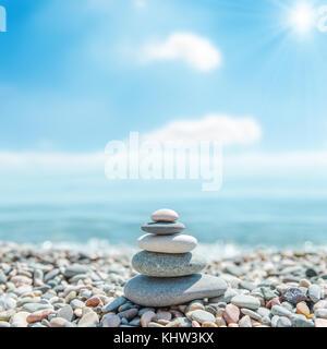 Stapel von zen Steine in der Nähe von Meer und Wolken mit der Sonne im Hintergrund - Stockfoto
