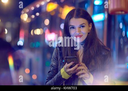 Junge Frau draußen in der Nacht, Smartphone, Tattoos auf Hals und Hand - Stockfoto