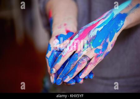 Die Hand des Künstlers mit einem dünnen Pinsel Abblendlicht hell fluoreszierenden Acrylfarben. blau, pink, türkis. - Stockfoto