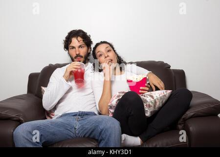 Romantisches Paar schaut Film zu Hause. Er trinkt ein Soda und Sie isst Popcorn auf dem Sofa im Wohnzimmer sitzen. - Stockfoto