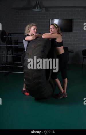 Fitness Frauen stellen in der Nähe eines Reifens in der Turnhalle. - Stockfoto