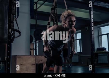 Kräftigungsübungen. Ein Mädchen tut eine Übung auf der Rückenmuskulatur in der Turnhalle - Stockfoto