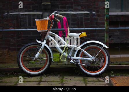 Weiß stützte sich Mädchen Fahrrad angekettet außerhalb - Stockfoto