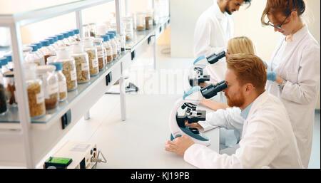 Gruppe von Wissenschaftlern für die Forschung durch Mikroskop - Stockfoto
