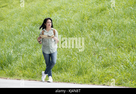 Asiatische Reisende mit Rucksack, offene Karte und freuen uns Richtung auf der Straße in der Nähe von grünen Gras - Stockfoto